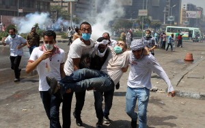 Supporters of deposed Egyptian President Mohamed Mursi carry a protester injured during clashes with riot police and army at around the area of Rabaa Adawiya square, where they are camping, in Cairo